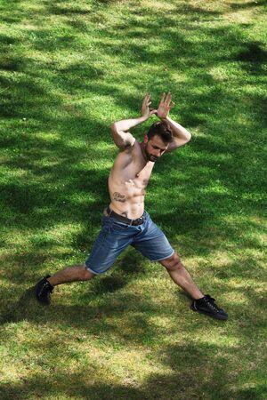 Male dancer portraying animal in dance in park 版權商用圖片 - 127363314