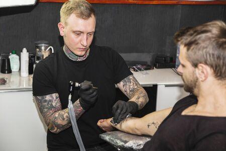 Man with tattoo working on creating new tattoo Stock fotó