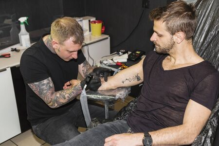 Professional tattooer doing picture on hand of man