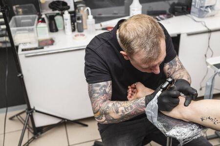 Young blonde tattoo artist makes tattoo in salon Stock fotó