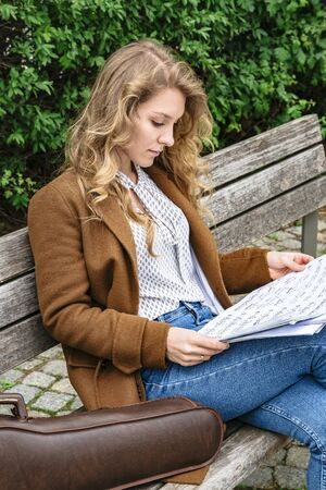 Girl studies music notes sitting on bench in park
