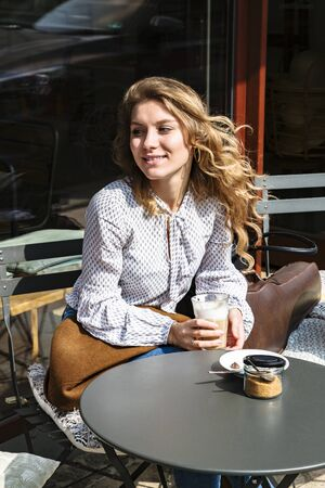 Girl sits in cafe with violins and drinks coffee