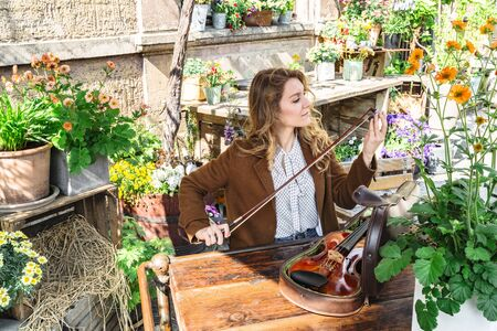 Girl in garden among plants adjusts bow for violin Banque d'images - 129478790