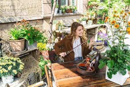 Girl in garden among plants adjusts bow for violin Banque d'images - 129478789