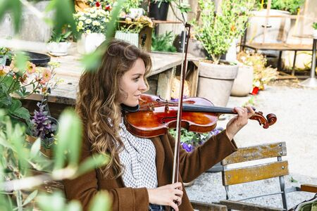 Profile of girl playing violin in autumn garden Banque d'images - 129478787