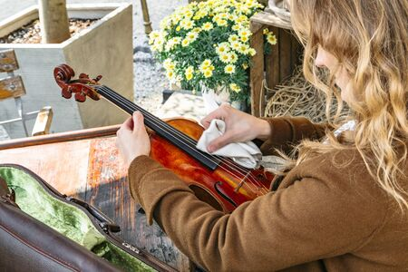 Girl takes violin from case and rubs for playing Banque d'images - 129478840