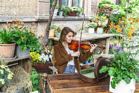 Young girl among colorful flowers playing violin Banque d'images - 129478836