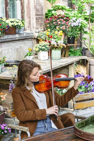 Girl with violin sitting outdoors among flowers Banque d'images - 129478838