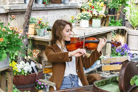 Young girl among colorful flowers playing violin