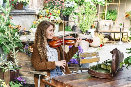 Young girl sits on wooden chair and plays violin Banque d'images - 129478842