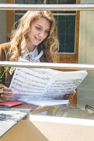 Girl sitting in cafe and reading musicians notes Banque d'images - 129478845