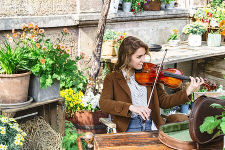 Young woman sits in autumn garden playing violin Banque d'images - 129478873