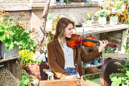 Young woman sits in autumn garden playing violin Banque d'images - 129478882