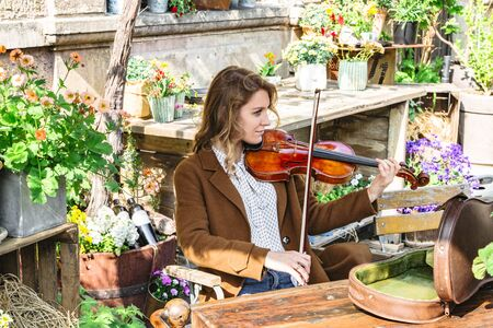 Young woman sits in autumn garden playing violin Banque d'images - 129478886