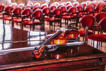Violin lies on piano on backround of blurred hall Banque d'images - 129478887
