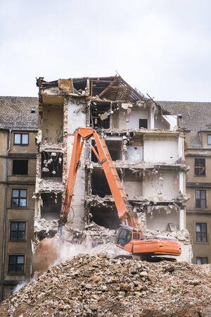 Old building demolition with hydraulic orange excavator