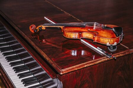 Violin with bow lying on piano on brown background Banque d'images - 129478941