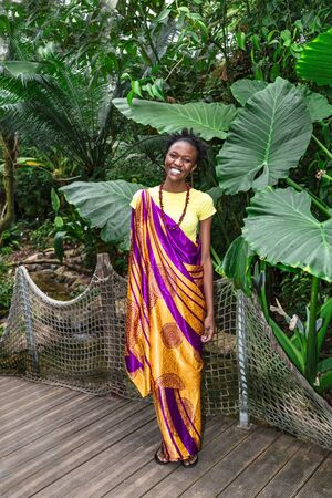 Young african girl stands and smiles in greenhouse Stockfoto