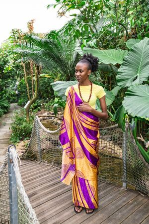 Young african woman in greenhouse among green trees