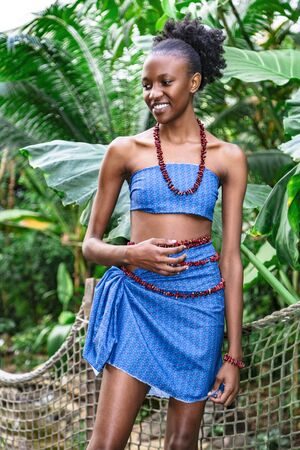 Beautiful sexy african girl in blue national clothing standing among green jungle