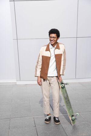 Fulllength shot of afro skater man with skateboard