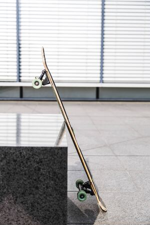 Skateboard leans against stand on white background