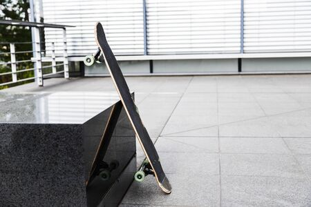 Skateboard leaned against granite stand on street and reflected in it