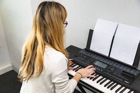 Young girl plays song on notes on synthesizer