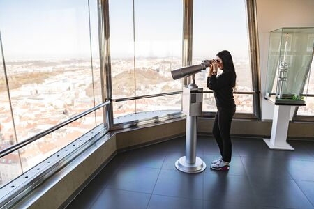 Girl looks in telescope in observatory in Prague