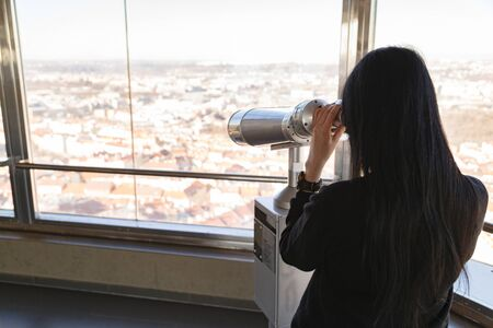 Woman brunette looks through telescope center of Prague city