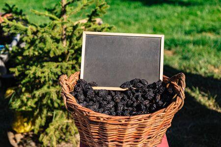 Basket full of oval shaped black prunes on field