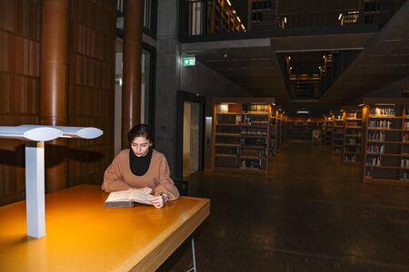Une fille lit un livre à la lumière d'une lampe assise à table