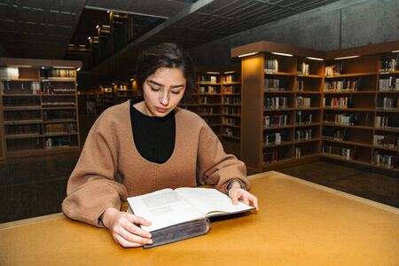 Young student girl reading book in library alone