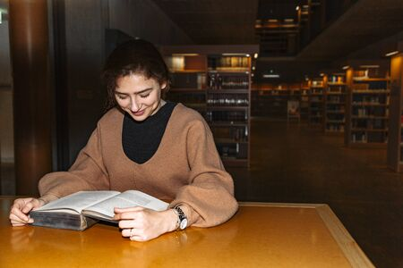 Young woman attentively reads book in library