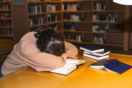 Tired female student sleeping in library at table Stok Fotoğraf