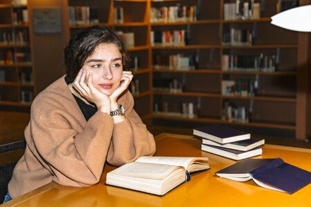 Girl in library sitting over books and thinking