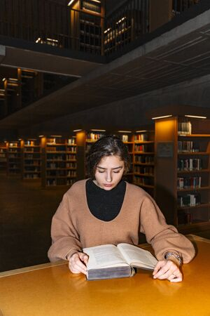 Girl bent over book sitting in library alone 写真素材