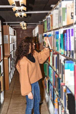 Young student stands in library and pulls out book