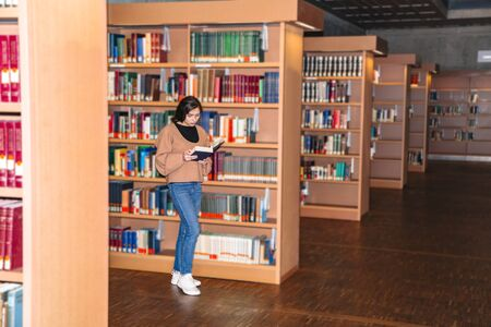 Young girl standing in library near bookshelves