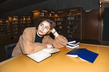 Girl sits above open book and looks into distance