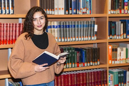 Smiling girl standing near bookcase with book