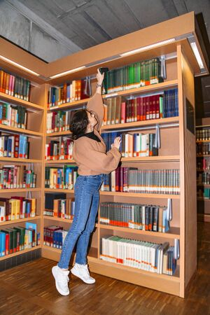 Young girl pulls book from top shelf of bookcase