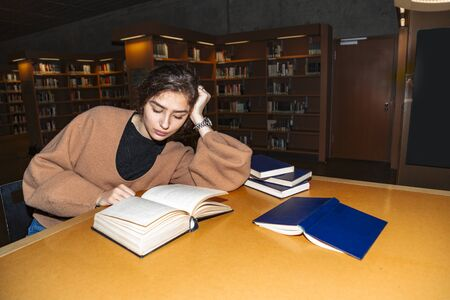 Young brunette thoughtfully reads book in library Stok Fotoğraf