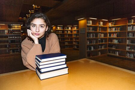 Young woman sitting near stack of books by table