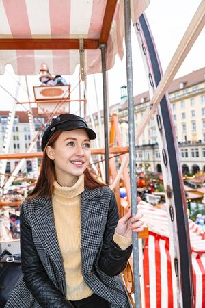 Young girl rides on ferris wheel and looks up Stockfoto
