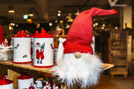 Ceramic mugs or jars with lids with Santa Claus painted on them standing on wooden stand Stock fotó