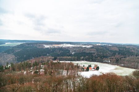 Glade with farm in snow in middle of winter forest