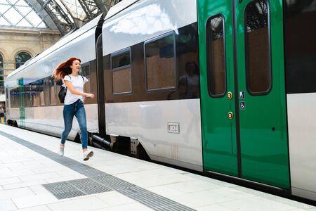 Frau am Bahnhof eilt zum Elektrozug