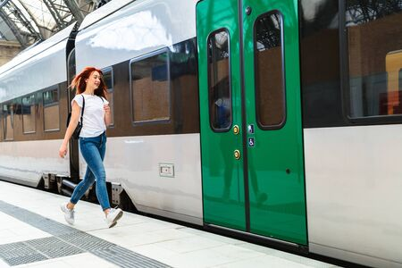 Woman at train station hurries to electric train