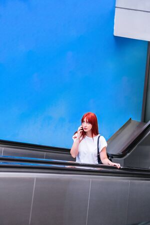 Young girl stands on escalator in station or metro